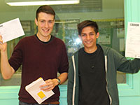 Two students holding up their A-level results