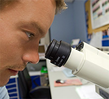 Man looking into microscope