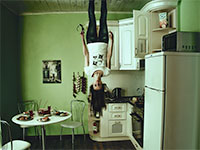 Woman standing on ceiling of apartment