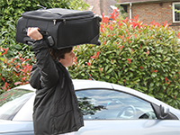 A student carrying a suitcase on his head