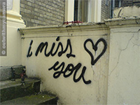 Graffiti on a wall reads: 'I miss you'