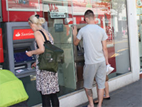 People getting money out from a cash machine