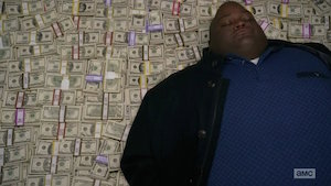 Man lying on pile of cash