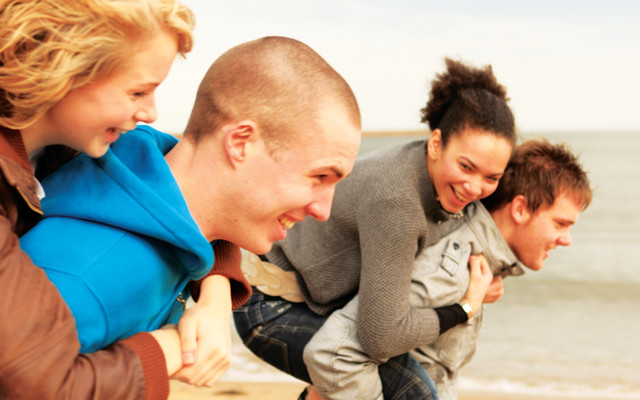 File:Students on beach piggybacks.jpg