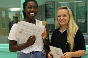 Two students celebrate after receiving their A-level results