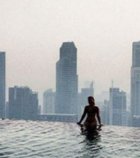 A student sits on the edge of an infinity pool looking at a city skyline