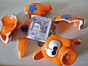File:Broken-piggy-bank-with-cash-spilling-out.jpg