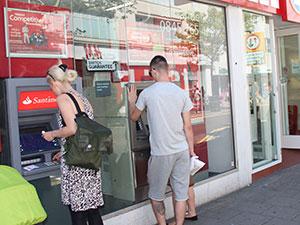 File:People-using-a-cash machine.jpg